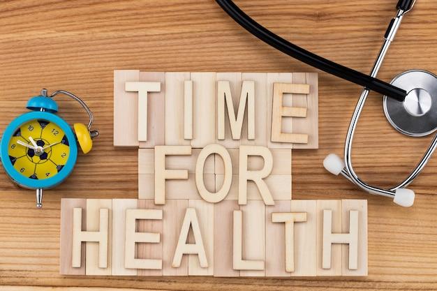 Время для здоровья - текст старинными буквами на деревянных блоках со стетоскопом и будильником. концепция медицины.