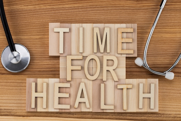 Время для здоровья - текст старинными буквами на деревянных блоках со стетоскопом. концепция медицины.