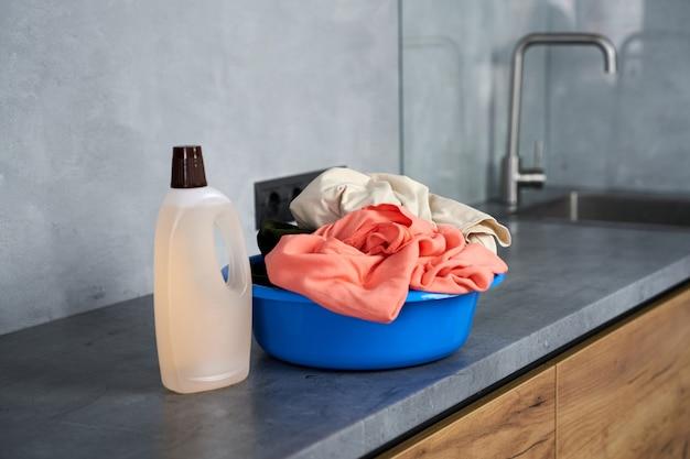 洗濯の時間。屋内で汚れた洗濯物と液体洗剤とプラスチックバスケットのショットをクローズアップ。ハウスワークとハウスキーピングのコンセプト