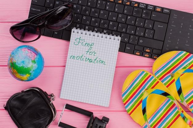 ピンクのテーブルトップの背景に女性の旅行者アクセサリーメガネ財布とマルチカラービーチサンダルでノートブックのモチベーションの時間。グローブと黒のキーボード。