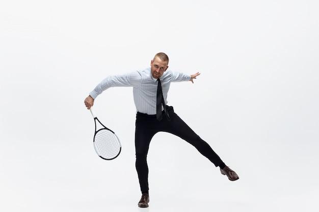 Время для движения. человек в одеждах офиса играет теннис изолированный на белизне. бизнесмен, обучение в движении, действия. необычный вид для спортсмена, новое занятие. спорт, здоровый образ жизни.