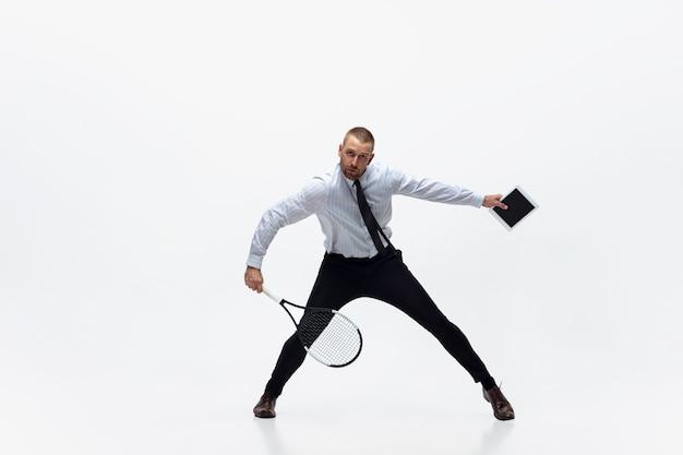 사무실 옷을 입은 남자가 흰색 스튜디오 배경에 격리된 테니스를 치는 시간