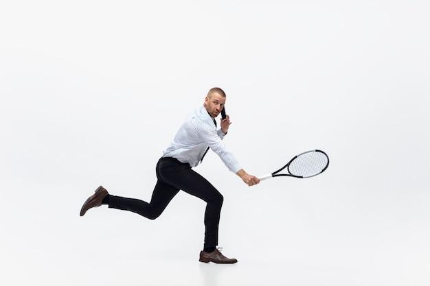 Время для движения. человек в офисной одежде играет в теннис, изолированные на белом фоне