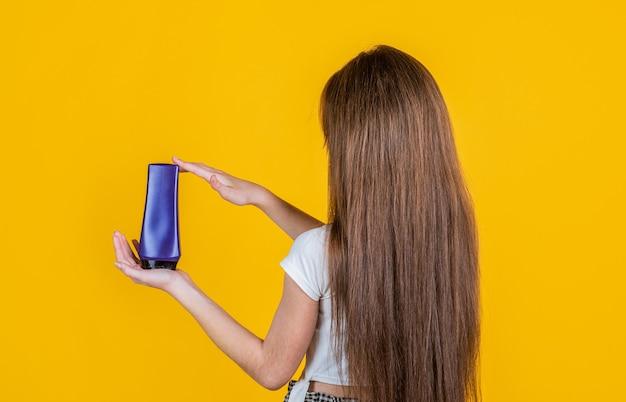 새로운 이발을 위한 시간. 강하고 탄력적입니다. 스트레이트너와 소녀 상태 머리입니다. 샴푸로 머리를 청소하는 십대 아이. 샤워 젤을 제시 하는 아이. 바디 케어 화장품 목욕 샤워. 스킨 로션.