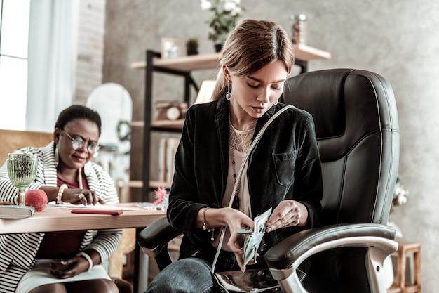 ペイオフの時間。財布からお金を取り出して黒いジャケットを着ている若い長髪の若い女性