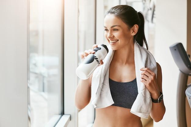 彼女の肩に白いタオルでスポーツウェアの若くて陽気な女性の休息の時間