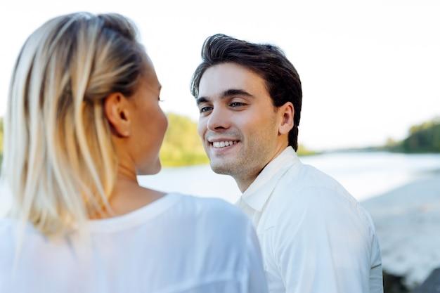 ロマンスの時間。川の近くで彼女と一緒に座っている間彼の妻に微笑んで陽気なハンサムな男