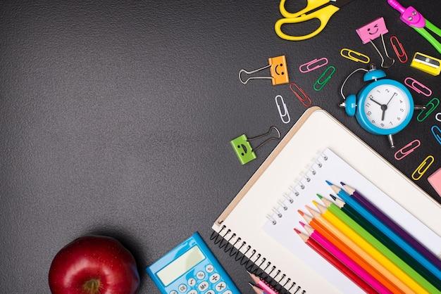 学校のコンセプトの時間。カラフルな文房具と黒板のコピースペースの空の空白で分離されたリンゴの俯瞰写真の上の上