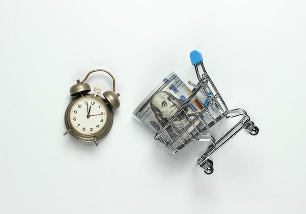 쇼핑 시간. 100 달러 지폐, 흰색 배경에 알람 시계와 쇼핑 카트