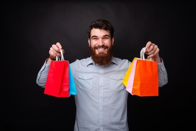 쇼핑할 시간! 수염을 기른 젊은 남자가 검은색 배경에서 쇼핑하기 위해 5개의 다채로운 종이 가방을 들고 있습니다.