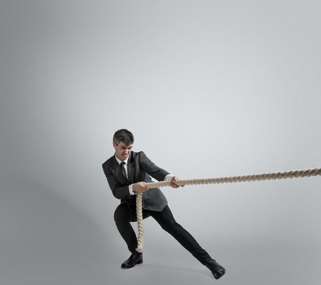 Время для сил. человек в тренировке офисной одежды с веревками на серой стене. получите цель, преодоление проблем, сроки. бизнесмен в движении, действии. спорт, здоровый образ жизни, работа.