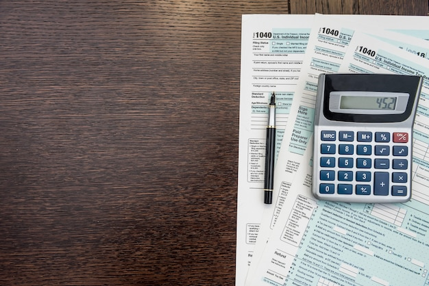 納税の時期、ペンと電卓を備えた連邦書式、事務机