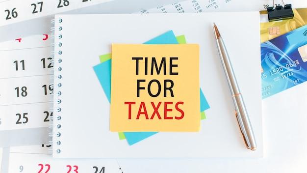 Время для налогов добавлено написано на желтой бумаге квадратной формы. кредитные карты, ручка, канцелярские товары на белом рабочем столе. концепция бизнеса, финансов и образования. выборочный фокус.