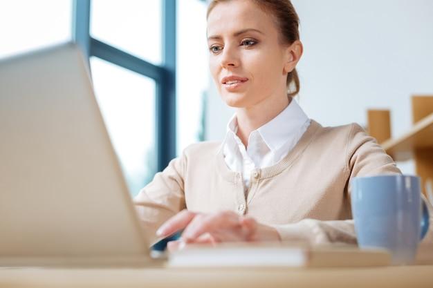 働く時間。テーブルに座って興味を示しながらラップトップで作業する若い秘書