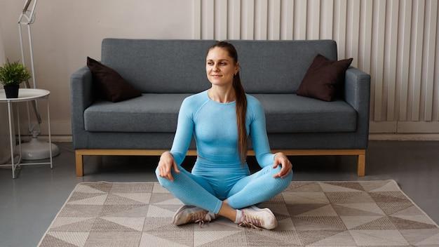 Время для йоги. привлекательная молодая женщина упражнениями и сидя в позе йоги, отдыхая дома
