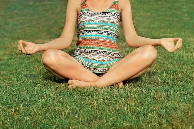 ヨガの時間です。運動とヨガの蓮華座に座っている美しい魅力的な若い女性。瞑想。アクティブなライフスタイル。健康とヨガのコンセプトです。フィットネスとスポーツ