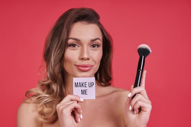 あなた自身のための時間。ピンクの背景に立っている間笑顔と化粧ブラシを適用する美しい若い女性