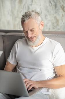 Время для себя. улыбающийся бородатый мужчина в белой футболке за ноутбуком в постели в хорошем настроении