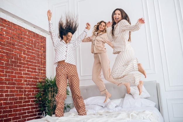 Time for fun. three young girls jumping on bed and feeling amazing