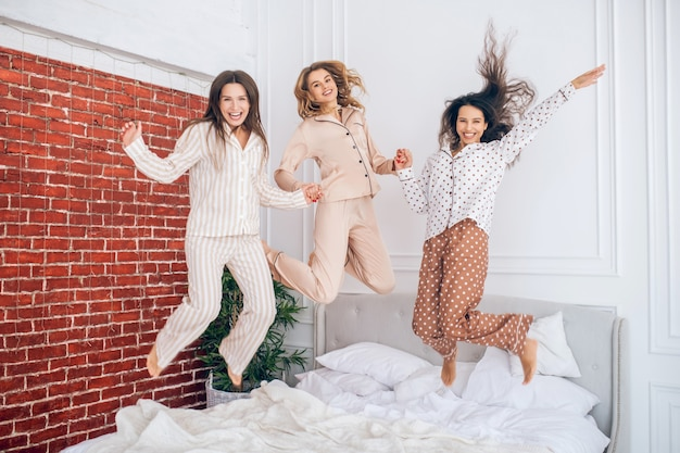 Time for fun. young girls jumping on bed and feeling awesome