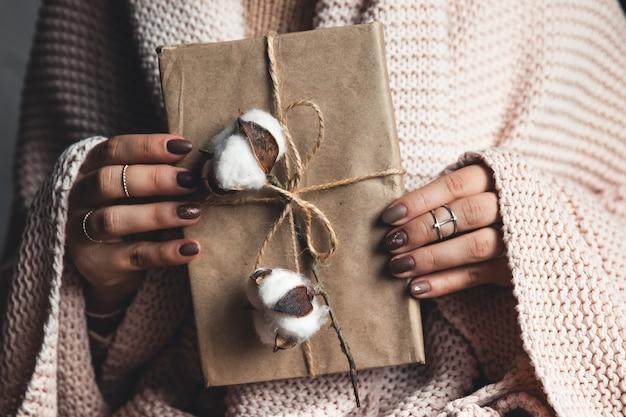 시간 선물-여자 손에 선물 상자. 여자의 손에있는 선물. 격자 무늬, 면화, 매니큐어. 발렌타인 데이