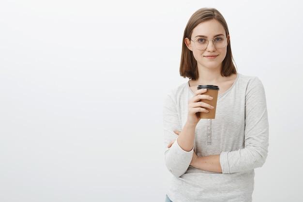 生産性を高めるためにコーヒーを飲む時間。メガネとブラウスの飲み物の紙コップを持って、灰色の壁を越えて流行に敏感なカフェを訪問して微笑んで満足してリラックスした、うれしそうな見栄えの良い女性