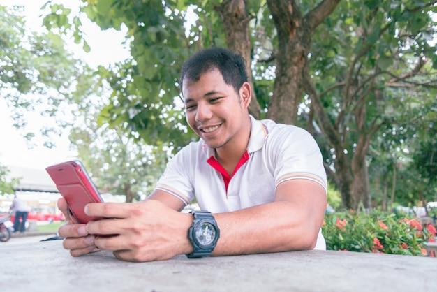 夕方time.he近くの公園のテーブルで携帯電話を使用して中年のアジア人は幸せな瞬間に見えます。モバイルデバイスを働く人々をリラックスの概念。