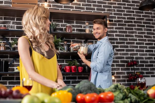 キッチンにいる時間。ハンサムな陽気なひげを生やした夫は、女性と台所で時間を過ごしながら微笑む