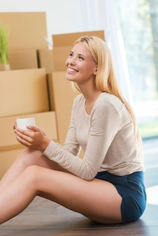 Time for inspiration. beautiful young woman sitting on the floor and holding cup of coffee while cardboard boxes laying in the background