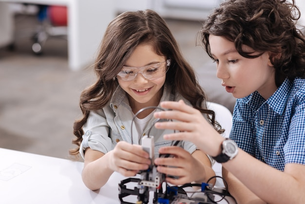 Time for inventions. inspired attentive delighted kids sitting in the laboratory and creating robot while expressing happiness