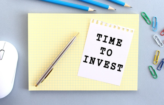 Time to invest is written on a piece of paper that lies on a notebook next to office supplies. business concept.