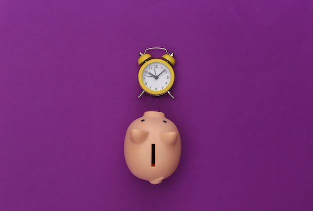 Time to invest. piggy bank, alarm clock on a purple background.