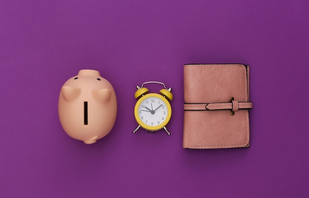 Time to invest. piggy bank, alarm clock an purse on a purple background.