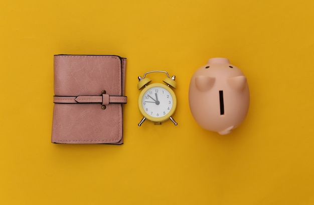 Time to invest. piggy bank, alarm clock and wallet on yellow background.
