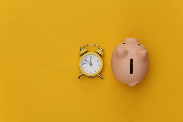 Time to invest. piggy bank, alarm clock on yellow background.