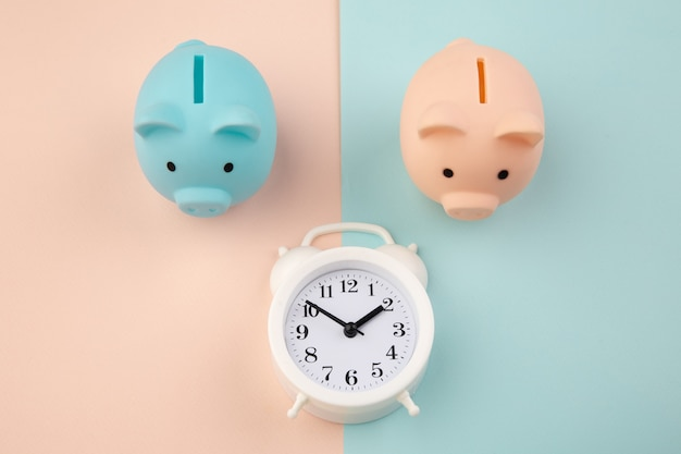 Time to invest. white clock and piggy bank on pink blue pastel.