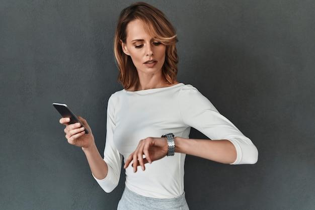 時は金なり。灰色の背景に立っている間時間をチェックし、携帯電話を保持しているスマートカジュアルな服装の美しい若い女性