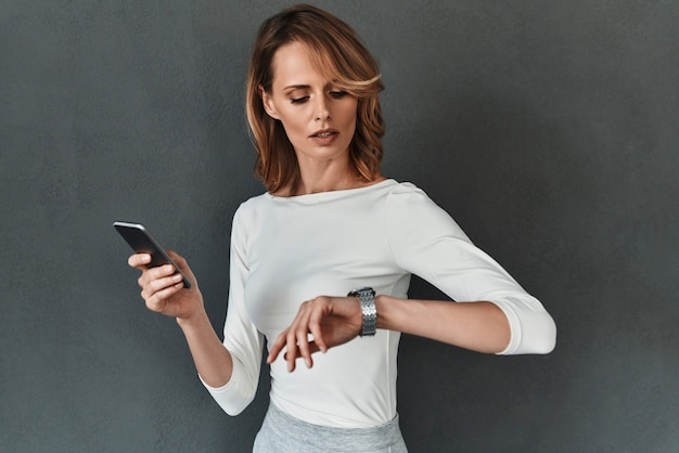 Time is money. beautiful young woman in smart casual wear checking the time and holding a mobile phone while standing against grey background