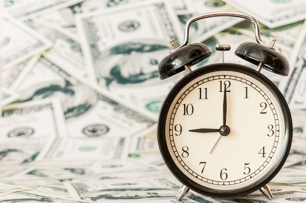 Time is money, clocks under background of american dollars.