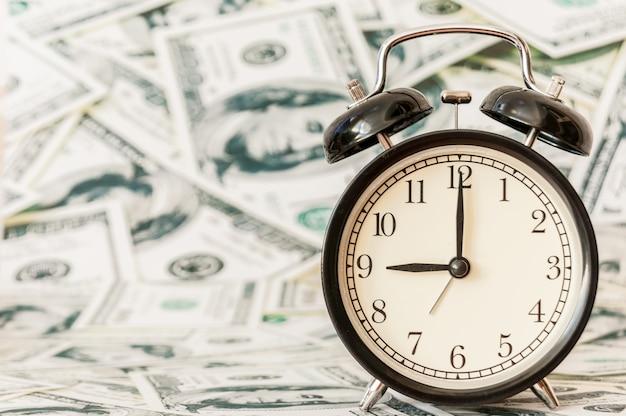 Время - деньги, часы на фоне американских долларов.