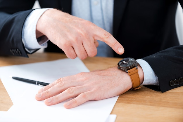 시간은 돈이다. 그의 작업 장소에 앉아있는 동안 그의 시계를 가리키는 사업가의 근접