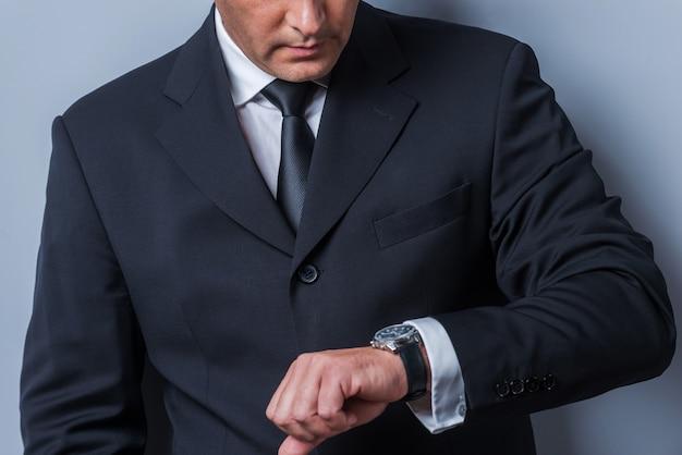 시간은 돈이다. 시계를 보고 회색 배경에 서서 시간을 확인하는 정장 차림의 자신감 있는 성숙한 남자의 클로즈업