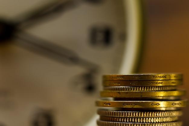 Время - деньги. крупный план сложенных монет и будильник.