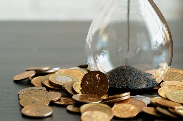 Time is money concept. close up of hourglass with money coins