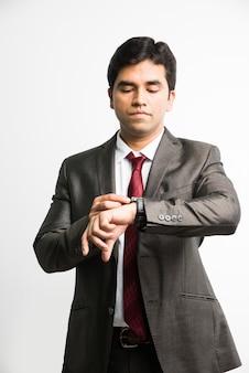 Время - деньги концепция - индийский азиатский молодой бизнесмен смотрит или устанавливает время в своих наручных часах, стоя изолированным на белом фоне