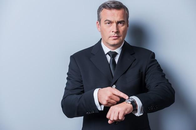 시간은 돈이다. 자신의 시계를 가리키고 회색 배경에 서있는 동안 카메라를보고 formalwear에서 자신감이 성숙한 남자