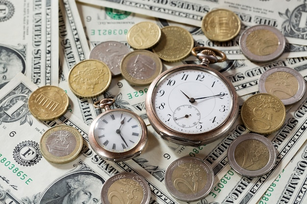 Time is money finance concept with old vintage clocks, dollar bills, spectacles