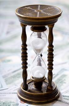 시간은 돈이다. 모래 시계와 미국 달러. 돈 개념 프리미엄 사진