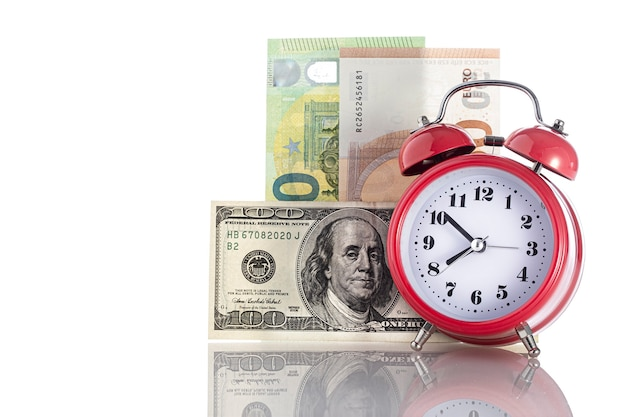 Время - деньги. ретро будильник на фоне стола и денег. бизнес-концепция финансовых идей с будильником. с бесплатным copyspace