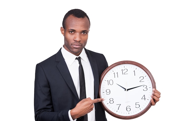 時は金なり!彼の手で時計を保持し、白い背景に孤立して立っている間それを指している正装の真面目な若いアフリカ人